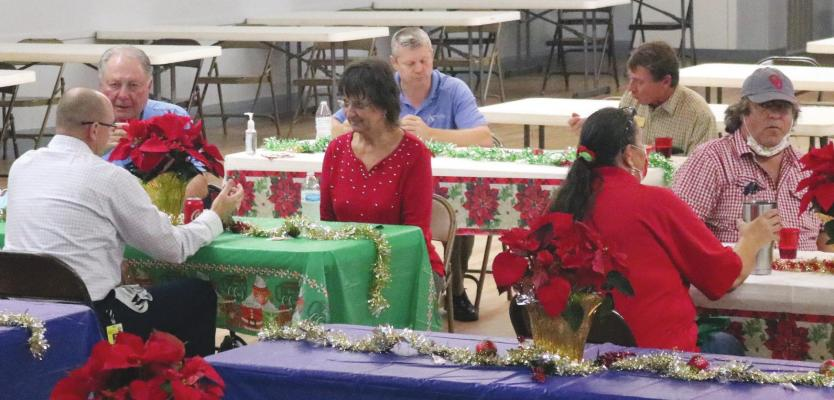 Guests visit each other during the annual holiday mixer hosted by the Sealy Chamber of Commerce Thursday at the American Legion hall. Joe Southern