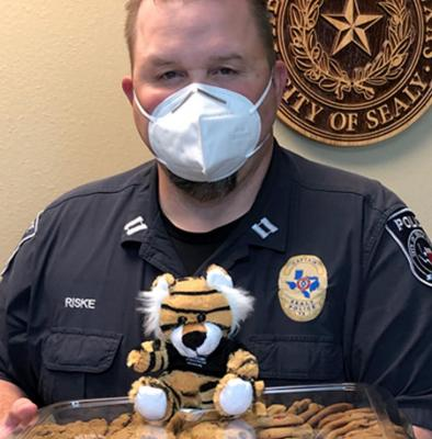 Officer Scott Riske from the Sealy Police Department receives cookies and a Sealy High School tiger for the Sealy Police Department from Brazos Valley Schools Credit Union in appreciation for all that the department does for the community. Contributed photo