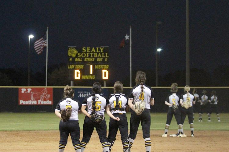 The Lady Tiger varsity softball team honors the flag while the National Anthem played to officially open the regular season last Tuesday at Sealy High School. (Cole McNanna/Sealy News)